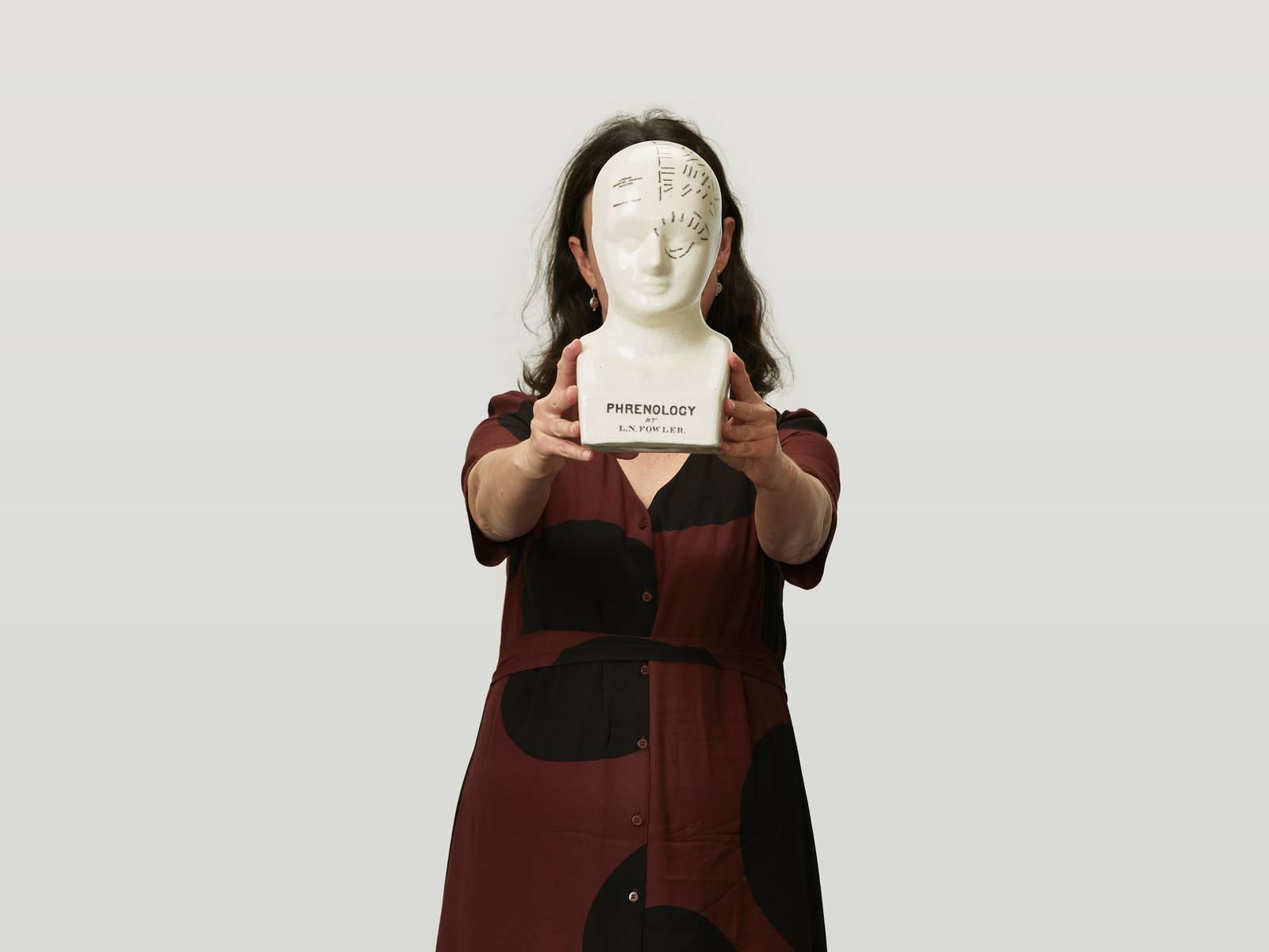 Virginia holding up a ceramic head.